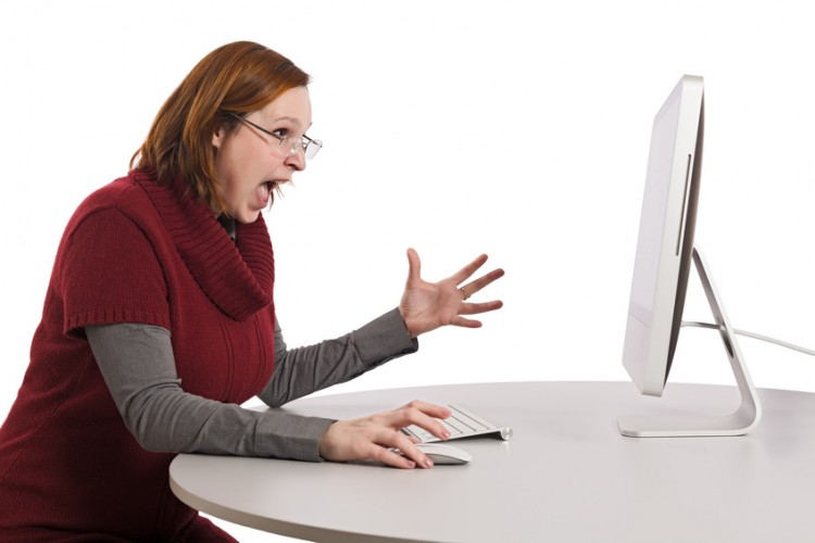 Young beautiful lady expresses anger and fury sitting in front of large computer screen. Smart casual dress, beige office desk, wireless keyboard and mouse, light grey background